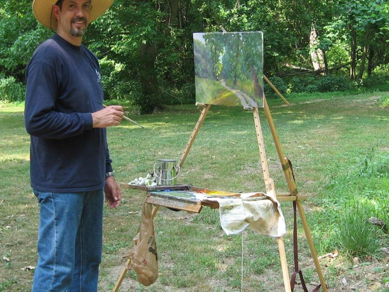 Armand Cabrera painting an oil painting, using his Take It Easel en plein air. The Take it easel supports her artwork and all her art supplies.
