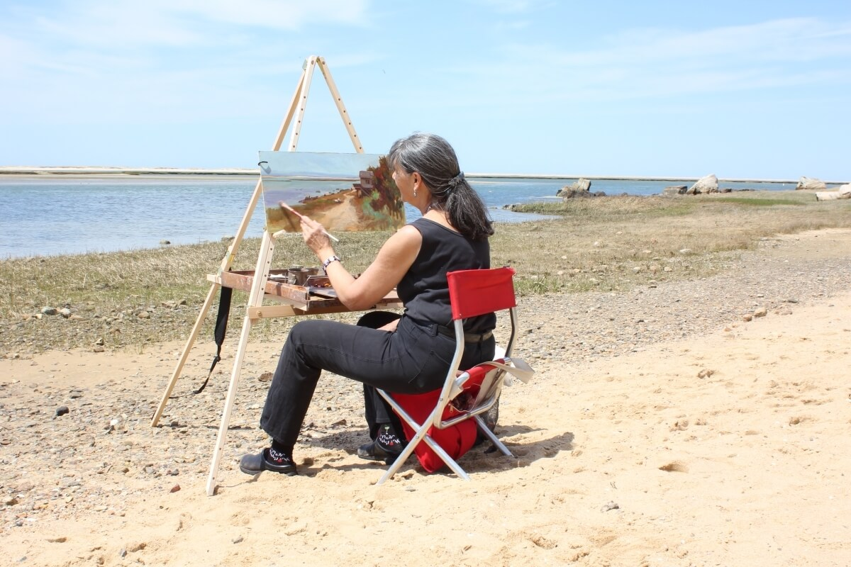 Rosalie Nadeau painting en plen air, painting while seated at her Take It Easel portable art easel