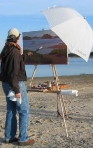 Rosalie Nadeau plein air painting on her Take It Easel, with an umbrella attached to her plein air portable easel